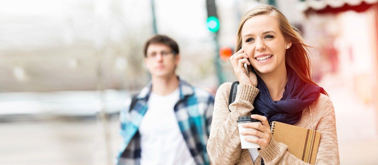 Junge Frau unterwegs mit Smartphone und Kaffeebecher